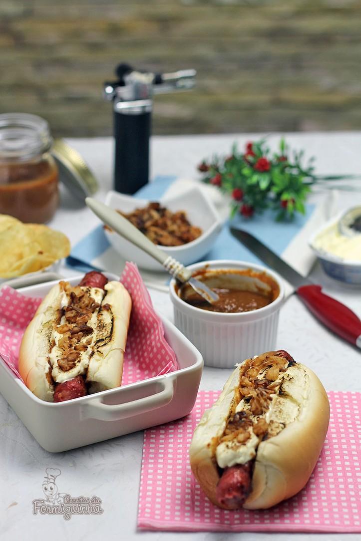 Sanduíche estilo food truck feito com linguiça defumada, molho barbecue de tomate pelado, cream cheese maçaricado no pão de cachorro-quente com cebola crocante (crispy).